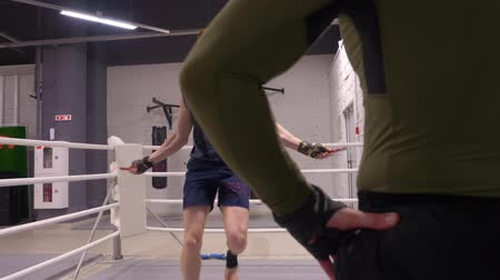 boksör : Professional workout with personal trainer, fighter is skipping on jumping rope on ringside crossing his hands.