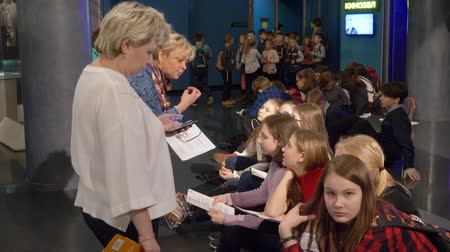 kiállítási tárgy : Moscow, Russia - March 21, 2019: children listening story of guide during school excursion in space museum. Woman expert talking with school pupil on excursion on space exhibition.