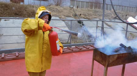 hasič : Elderly firefighter woman in a yellow raincoat puts on protective gloves and extinguishes the fire in the grill using fire extinguisher. Dostupné videozáznamy