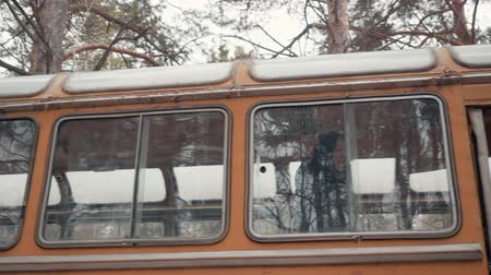 roto : Young woman in jacket came to the village and got off the old orange bus. Stock Footage