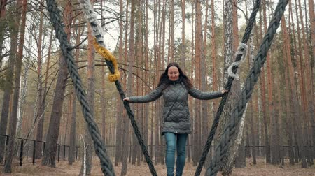 único : Woman in jacket is swinging on a huge wooden swing in city park with forest.