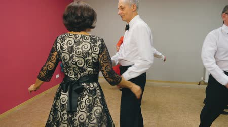 whirling : Elderly couples are dancing waltz in elegant clothes. Dance class for pensioners. Stock Footage