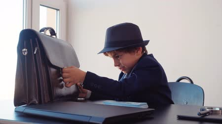 bolsas de papel : Little boy business boss at business table hiding money stack in briefcase in office. Young business boss in black suite and hat putting money cash in briefcase. Business children concept