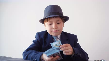 opsporing : Young businessman recounting dollar banknote and looking through magnifying glass. Scrupulous businessman checking money authenticity money with magnifier at table in business office
