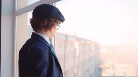nákrčník : Serious Caucasian Business Kid Look Office Window. Cute Child Boy in Glasses Dressed Classical Suit Wear Hat on Head. Adult Life Imitation Skyscraper Background Jobs Concept Side View 4K Dostupné videozáznamy