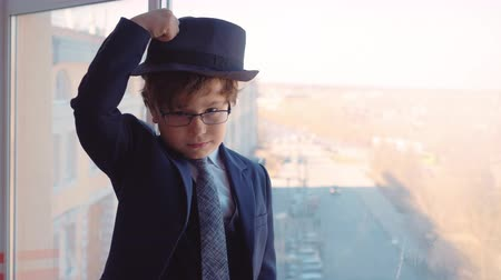 pet : Cute Boy Wear Businessman Suit Look Office Window. Nice Caucasian Child in Glasses Put on Hat Adult Life Parody. Serious Kid Business Strategy Skyscraper Background Occupation Concept Closeup 4K