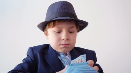 opsporing : Focused business boss checking money banknotes with magnifying glass in office. Amazed little boy looking hundred dollar bills through magnifier in business office. Business kids concept