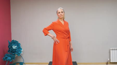 exclusivo : Senior woman in red dress walking on catwalk at fashion show. Elegant mature woman showing new designer clothes collection at fashion event. Elegance, style and vogue