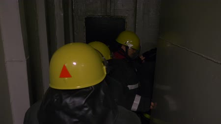 fire suit : Rescuers in protective clothing and yellow helmets go through the dark tunnel one after another, putting his hands on the shoulders in front of him. Rescue operation or exercise. Stock Footage