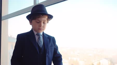 know : Little boy looks like a businessman in suit and hat is looking at window in his office standing back to camera, turning face and looking in watches on his hand.