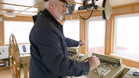 lever : Bearded gray haired captain of ship in peaked cap and uniform at work in ship cabin operates the ship with two levers. Shipping concept.
