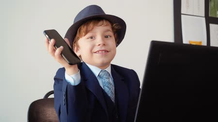 one hundred : Presentation shoe phone. Portrait of little boy looks like a businessman in his office with mobile phone in hand sitting at table with computer, putting money and talking. Business concept.