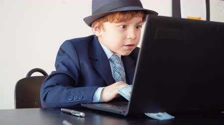имитация : Surprised young little entrepreneur. Portrait of happy small boy looks like a businessman working on computer and raises his hands up with smile on his face exulting of his success.