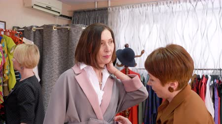 выбирать : Adult woman trying new coats in fashion store while shopping. Stylish woman choosing clothes in clothing showroom. Female shopping concept
