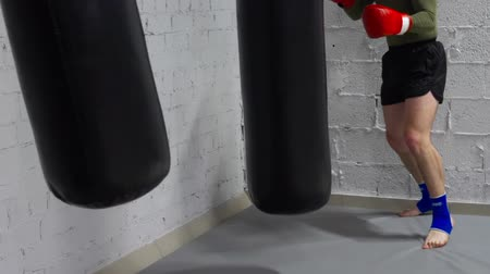 fight club : Kickboxer man training punches by combat bag in gym. Boxer man in gloves boxing to punching bag in fight club. Box training concept. Fitness lifestyle