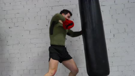 boksör : Man boxer in gloves punching combat bag by knees and elbows in boxing club. Sportsman training kick at kickboxing workout with punching bag. Fighting exercise. MMA concept