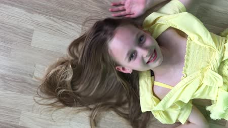 doğru : Carefree girl teenager lying down on wooden floor smiling to camera. Happy girl model posing front camera on wooden floor background. Right above top view