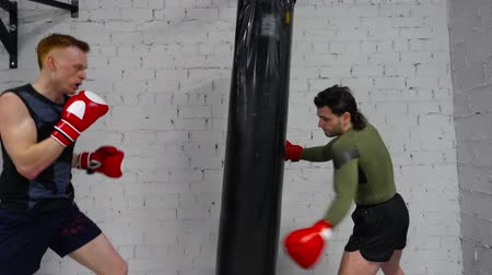 punching bag : Fighter man in boxing gloves making blows on combat bag while personal training. Fitness trainer training man boxing punching bag at fight in gym club. Cardio training