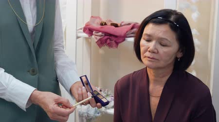 alapvető : Professional teacher visagiste training student to makeup for mature skin at master class in beauty school. Makeup for elderly woman. Beauty school concept Stock mozgókép