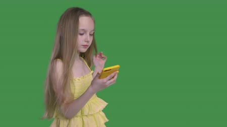 tenso : Teen cute girl in yellow dress with windy long hairs is browsing her smartphone standing on green screen background. File with alpha channel. Transparent keyed background