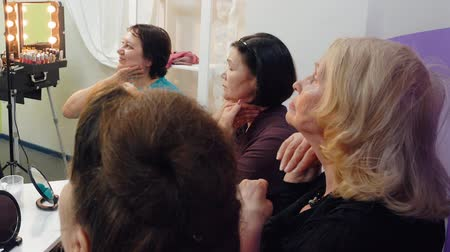 masaż twarzy : Senior women are learning to make face massage themselves in group with teacher on massage lesson in elderly club.