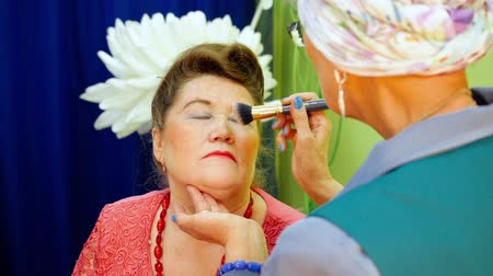 applying : Visagiste is doing makeup for senior woman. Applying a powder on the face using a brush in beauty studio. Beauty and makeup concept. Stock Footage