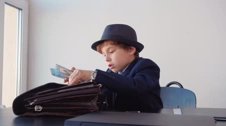 utánzás : Little boy in suit and hat looks like entrepreneur is sitting in his office. He is hiding the cash money to briefcase and do paper work.