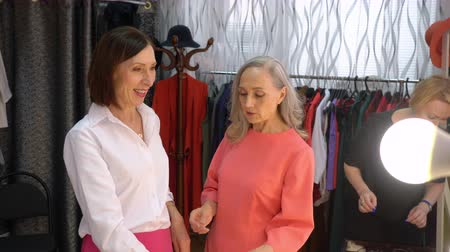 requintado : Mature woman brunette is trying on a bracelet with flower in clothing store. Seller consultant, elderly elegant woman, helps her with the choice.