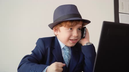 связать : Portrait of little angry boy looks like a boss is talking mobile phone in his office sitting at table. He is wearing suit and hat. Manager in office