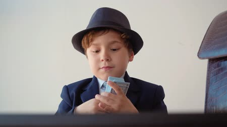 chapéu : Small boy looks like entrepreneur counts cash dollars sitting in his office. Opens his computer and starts to work on white background.