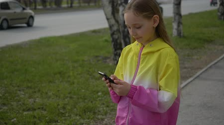 raport : Child teen girl is walking down the street and talking with camera holding smartphone in hands. She is flipping the web pages in the smartphone with green screen.