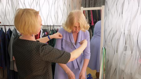 choise : Elderly blonde woman is trying on the necklace with stones in the clothes store. Seller consultant is helping her with the choice.
