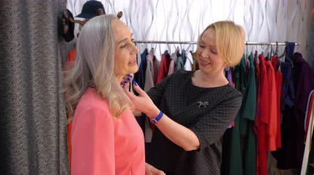 choise : Portrait of two women in shop. Seller consultant offers an elderly elegant grey-haired woman to try on earrings in store.