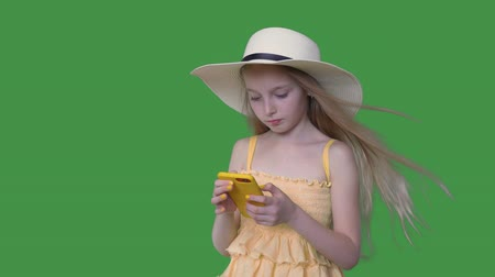 tenso : Young girl in hat and yellow dress using mobile phone on transparent green background. Summer girl with hair waving on wind browsing smartphone on green background. Alpha channel keyed green screen.