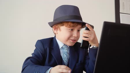 роль : Cute Kid Boss Manager Talks Mobile Phone Role Play. Little Caucasian Boy Sit Office Wear Classic Style Suit Hat on Head. Funny Child Act Professional Businessman Hold Smartphone Game Concept 4K