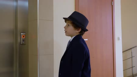 presleme : Kid boy looks like a businessman in suit and hat is waiting elevator, pressing the button and waiting a long time in his office. Adults life parody. Stok Video