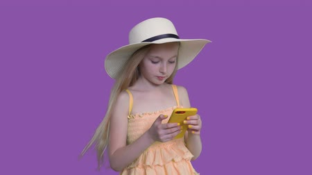 gadżety : Cute blonde pre-teen child girl with long hairs in summer hat and yellow dress. She is browsing mobile phone on purple wall background and touching a screen.