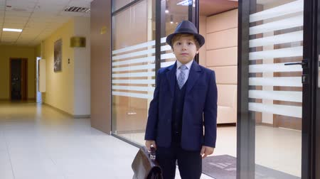 gravata : Little boy looks like a boss in suit and hat with briefcase in hand losted in big office. He cant find the exit. Adults life parody.