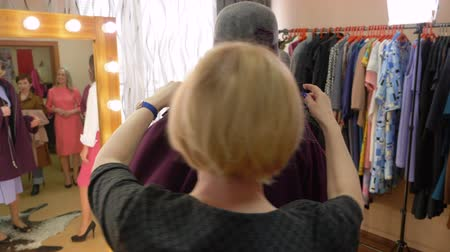 choise : Fashionable senior woman in hat is trying purple coat in clothes store and looking at mirror. Sales consultants help her with the choice.