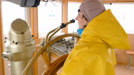 ステアリング : Senior woman in yellow raincoat rotates the steering wheel on the ship. She is in wheelhouse of the marine vessel. 動画素材