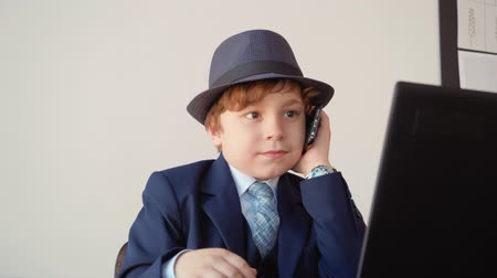 datore di lavoro : Little boy calling by mobile phone front laptop in business office. Young businessman talking by smartphone while business conversation at workplace in office. Business kids concept