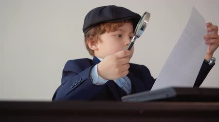 vizsgálat : Focused businessman researching paper document with magnifying glass in office. Concentrated business boss using magnifier for scrutinize. Detective investigating in bureau