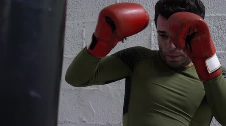 boksör : Boxer in boxing gloves kicking combat bag at fight training in fight club. Fighter man training by punching bag in box club. Fighting training. Mixed martial arts
