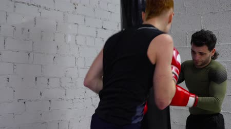 kickbox : Kickboxer training kick by boxing bag on kickboxing training. Boxerman in gloves doing punches to combat bag in fight club. Mixed martial arts. Fight training concept