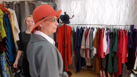 frizura : Elegant woman smiling and posing while fitting red hat in fashion showroom. Stylish mature woman choosing elegant hat in clothing boutique. Shopping concept