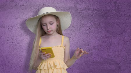 manicure : Girl Posing with Mobile Phone on Violet Lilac Background. Child in Hat and Yellow Dress Hold Telephone in Hand. Little Model in Stylish Look with Long Fluttering Hair. Stylish Teen in Fashion Studio Stock Footage