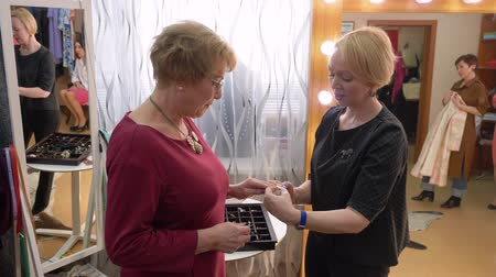 браслет : Senior Woman Choosing Bracelet in Fashion Store. Adult Lady in Stylish Dress and Glasses Try Jewelry in Shopping Center. Aged Female in Necklace Looking at Accessory at Boutique and Smiling