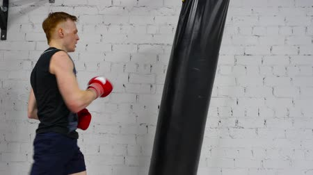 агрессивный : Boxer man training punches by combat bag in fight club. Professional boxer man in gloves boxing to punching bag in sport club. Box training concept. Fitness lifestyle. Legs kick