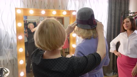 fashion outlet : Elegant woman choosing stylish hat in fashion boutique front mirror together seller. Mature woman trying new hat in accessories showroom. Shopping fashion sale. Female hobbies. Stock Footage