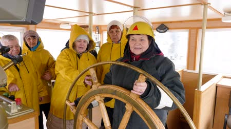 denizciler : Female captain and ship crew in navigation bridge. Mature woman captain of fishing ship turning steering wheel and sailors standing on background. Unusual female professions Stok Video